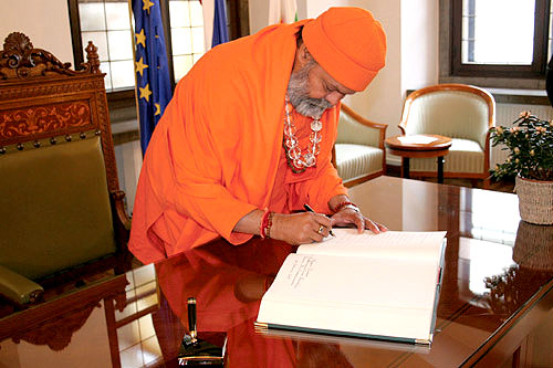 His Holiness Mahamandaleshwar Paramhans Swami Maheshwarananda is signing the Ljubljana\'s Town Hall Book of visitors