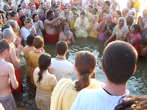 His Holiness Swamiji, surrounded by devotees, takes a holy dip in Ganges